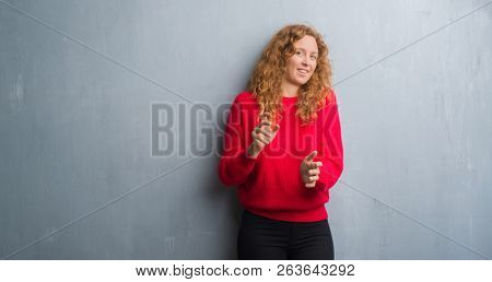 Young redhead woman over grey grunge wall wearing red sweater disgusted expression, displeased and fearful doing disgust face because aversion reaction. With hands raised. Annoying concept.