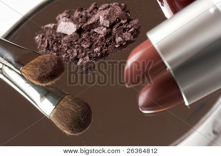 cosmetics reflection in the mirror, red lipstick, powder and brush