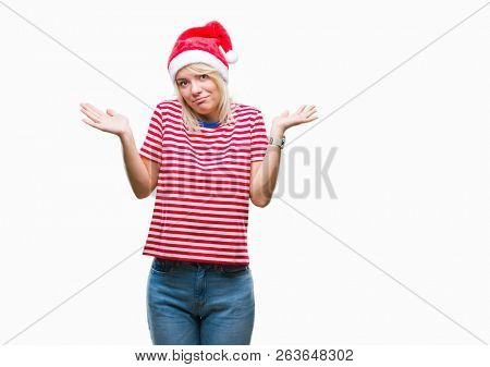 Young beautiful blonde woman wearing christmas hat over isolated background clueless and confused expression with arms and hands raised. Doubt concept.