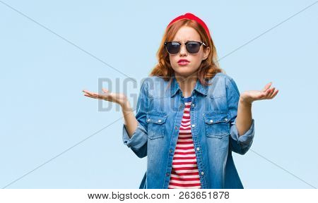 Young beautiful woman over isolated background wearing sunglasses clueless and confused expression with arms and hands raised. Doubt concept.