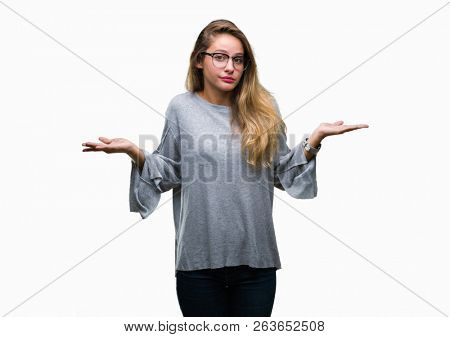 Young beautiful blonde woman wearing glasses over isolated background clueless and confused expression with arms and hands raised. Doubt concept.
