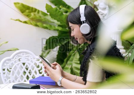 Concept Relax Time. Attractive Back Of Young Women Wearing White Headphones Enjoy Listening Music Fr