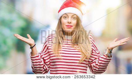 Young beautiful woman wearing christmas hat over isolated background clueless and confused expression with arms and hands raised. Doubt concept.