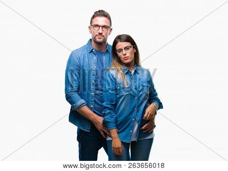 Young couple in love wearing glasses over isolated background with serious expression on face. Simple and natural looking at the camera.