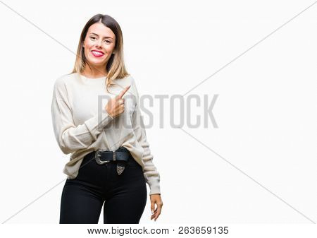 Young beautiful woman casual white sweater over isolated background cheerful with a smile of face pointing with hand and finger up to the side with happy and natural expression on face
