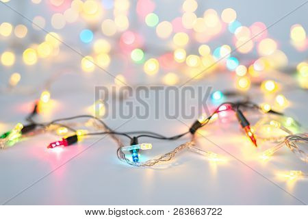 Christmas Lights In Warm Yellow White On String And Gold Xmas Balls Over Light Background With Copy