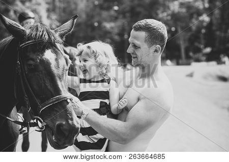 Friend, companion, friendship. Girl with man pet horse on sunny day. Child with muscular macho smile to animal. Equine therapy, recreation concept. Happy childhood, fathers day. poster