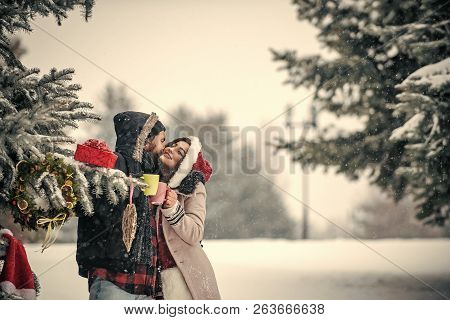 Christmas Couple Of Happy Man And Woman Drink Hot Wine. New Year Girl And Guy In Snowy Forest. Winte