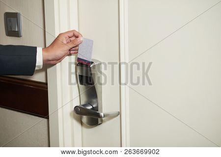 Crop Hand Of Man In Suit Inserting Card Into Door Lock Entering Hotel Room