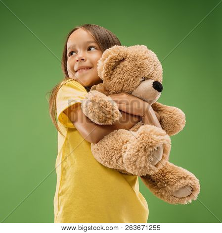 Happy Teen Girl Standing, Smiling With Toy Bear Isolated On Trendy Studio Background. Beautiful Fema