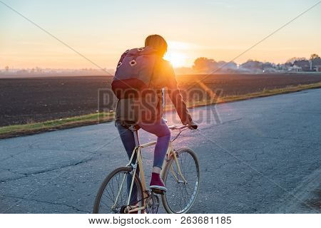 Female Commuter Riding A Bike Out Of Town To A Suburban Area. Woman Cycling Along The Road At Sunset