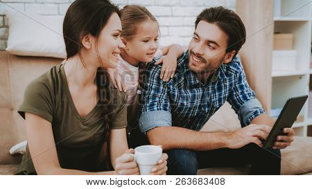Happy Family. Parents And Daughter. Family Resting Together. Happy Child And Parents. Tablet In Fath