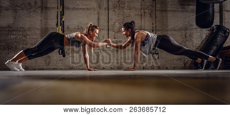 Two Young Muscular Girls Doing Plank Exercise At The Hard Workout.
