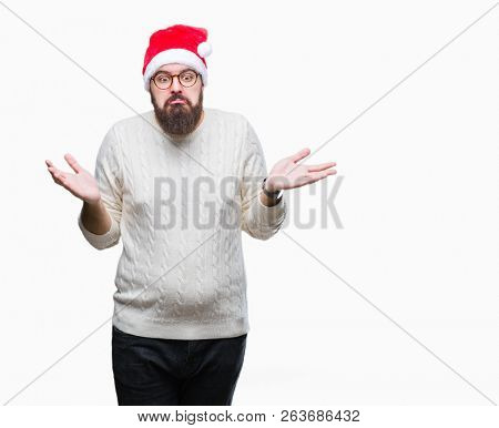 Young caucasian man wearing christmas hat and glasses over isolated background clueless and confused expression with arms and hands raised. Doubt concept.