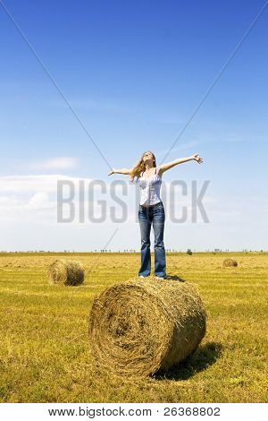 girl standing on a straw roll spreading her hands towards the sky