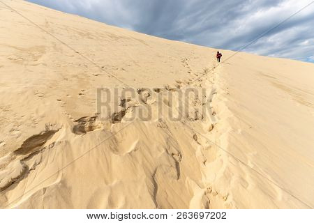 Woman climbing the huge Pyla sand dune in the Arcachon bay, Aquitaine, France
