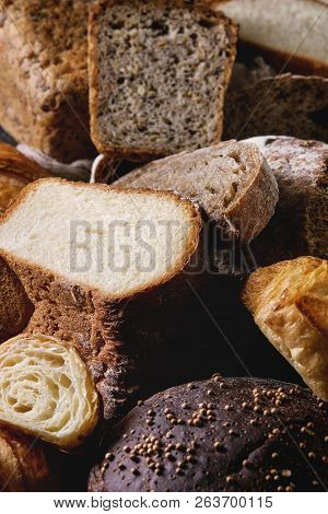 Variety of fresh baked rye, spelled, wheat craft artisan bread, whole and sliced, on black texture background. Close up poster