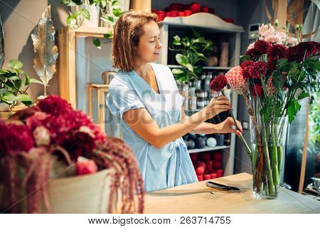 Female florist puts flowers in a vase, floral shop
