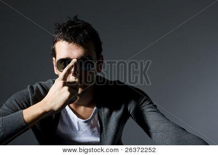 studio shot of a young man wearing sunglasses