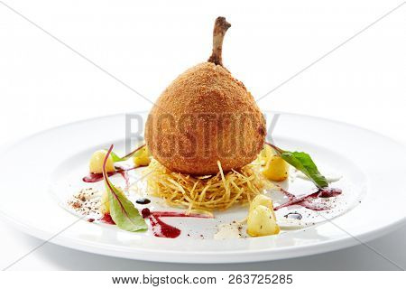 Fried chicken Kiev or cutlet Kiev-style made of chicken fillet pounded and rolled around cold butter, coated with bread crumbs. Beautiful creative food design on white plate with spices and sauce