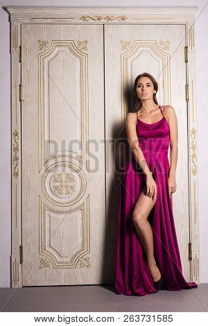 Fashion Portrait Of A Woman Posing In A Beautiful Evening Dress, Near The Big White Doors. Luxurious