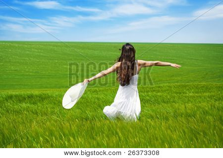 girl in green field with open arms dancing and enjoying nature
