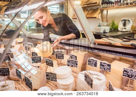 Shop clerk woman sorting cheese in the supermarket display to sell it poster