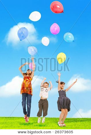 children jumping and playing with balloons outdoors in summer field