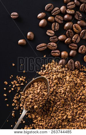 The instant coffee and coffee beans on black table.
