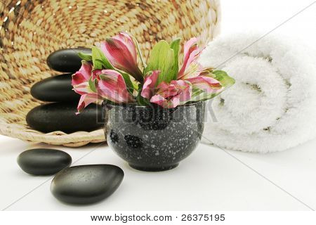 Spa products. Towel, massage stones and exotic flower