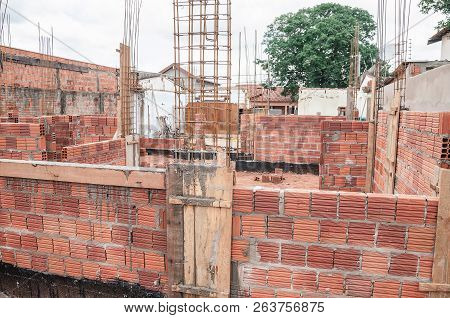 Construction, land under construction of a masonry house. Structure of reinforced concrete. House made of bricks, steel rebars and concrete. Structural parts of a house. poster
