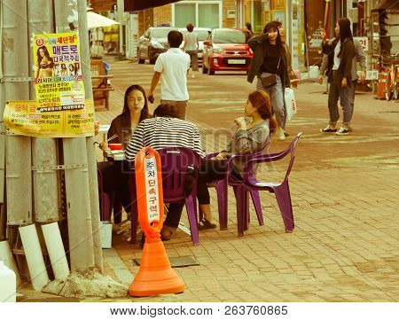 Samcheok, South Korea; September 24, 2018: Three Young Unidentified Koreans Eating At Sidewalk Table