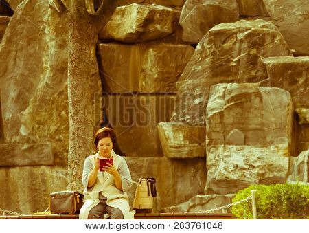 Samcheok, South Korea; September 24, 2018: Young Unidentified Korean Woman Using Cellphone While Sit