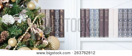 A Beautiful Decorated Christmas Tree On The Background Of A Bookshelf With Many Books Of Different C
