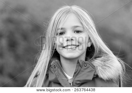 Girl With Blond Long Hair Smile On Natural Environment. Child In Red Coat Enjoy Idyllic Autumn Day.