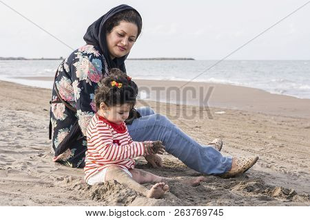Mother And Young Child With Diaper At Beach, Care And Watchfulness Concept