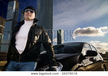 Tough guy in leather jacket near his car and skyscrapers at background