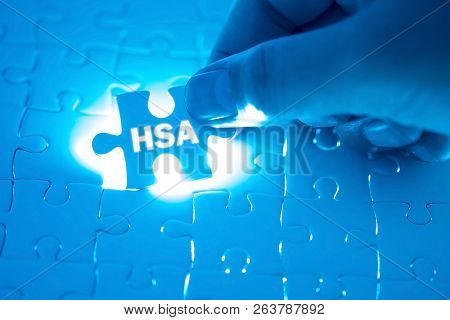 Doctor Hand Holding A Jigsaw Puzzle With Hsa (health Savings Account). Medical Concept