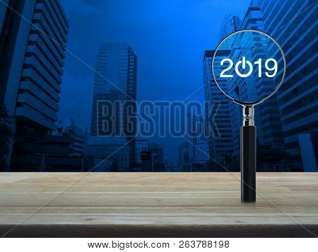2019 Start Up Flat Icon With Magnifying Glass On Wooden Table Over Modern Office City Tower And Skys