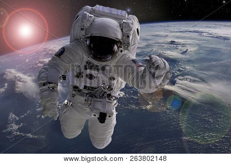 Astronaut Flying In Outer Space Near Planet Earth Doing Some Work Near Space Ship, Elements Of This