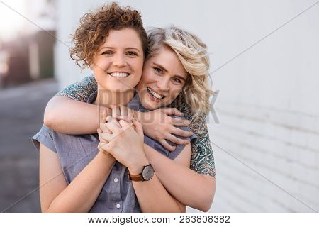 Smiling young lesbian couple standing affectionately together outdoors poster