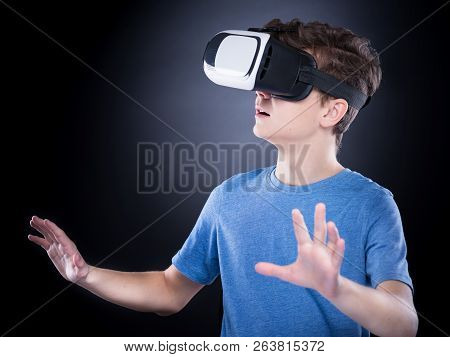 Happy Teen Boy Wearing Virtual Reality Goggles Watching Movies Or Playing Video Games. Cheerful Smil