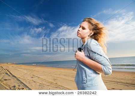 Young woman listen music with closed eyes at sunny day at seahore