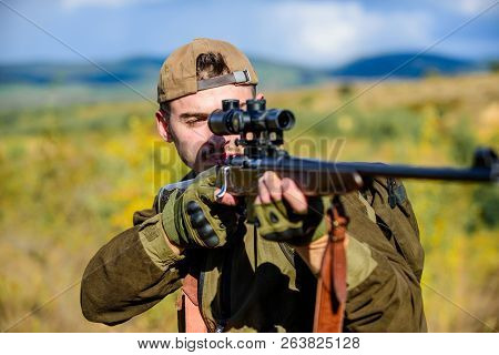Looking at target through sniper scope. Man hunter aiming rifle nature background. Hunting skills and weapon equipment. Guy hunting nature environment. Hunting weapon gun or rifle. Hunting target poster