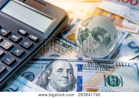Global Business And Economy. World Globe Crystal Glass And Calculator On Various International Money