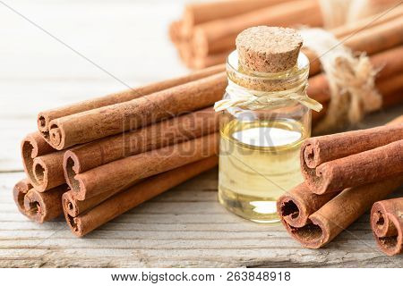 Cinnamon Oil And Cinnamon Sticks On The Wooden Board