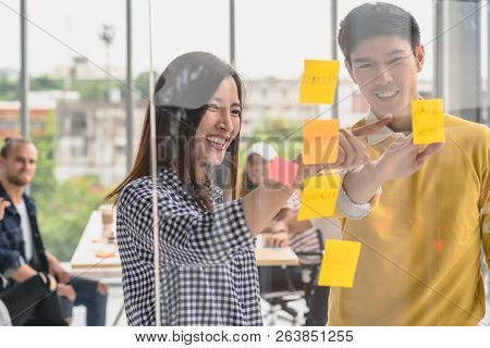 Couple Of Creative Colleague Writing And Pointing The Postit On The Millor Board When Presenting The