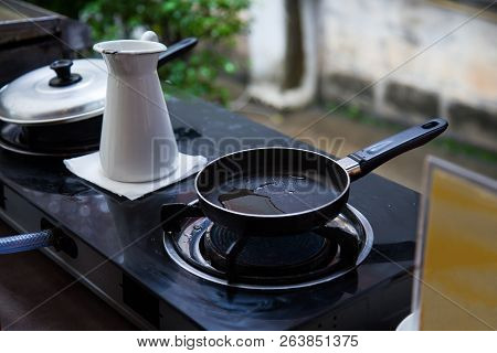 Heating Oil In Stainless Steel Pan On Gas Fueled Stove, Prepared For Frying Breakfast Or Lunch Food