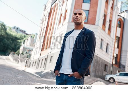 Outdoors Leisure. Young Man Standing On The City Street Hands In Pockets Looking Aside Cool