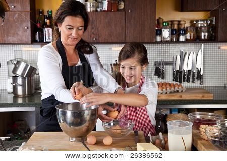 Mother And Daughter Baking Together In The Kitchen